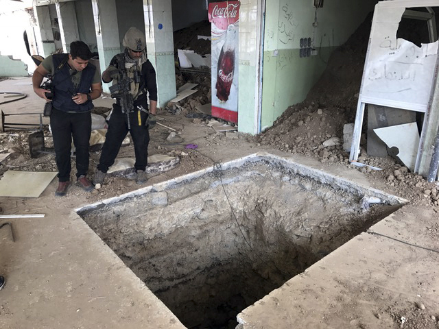 A soldier with Iraq's elite counterterrorism force, left, inspects a tunnel made by Islamic State militants in Bartella, Iraq, Thursday, Oct. 27, 2016. The town of Bartella in northern Iraq lays a ...