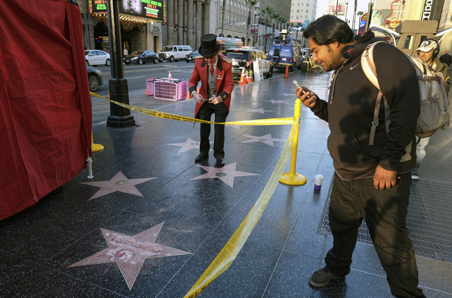 A man takes a photo of the vandalized star for Republican presidential candidate Donald Trump on the Hollywood Walk of Fame, Wednesday, Oct. 26, 2016, in Los Angeles. (Richard Vogel/AP)