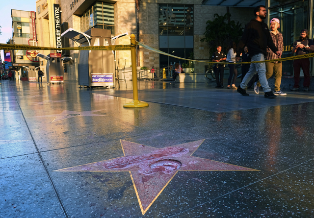 Pedestrians walk past a cordoned off area surrounding the vandalized star for Republican presidential candidate Donald Trump on the Hollywood Walk of Fame, Wednesday, Oct. 26,2016, in Los Angeles. ...