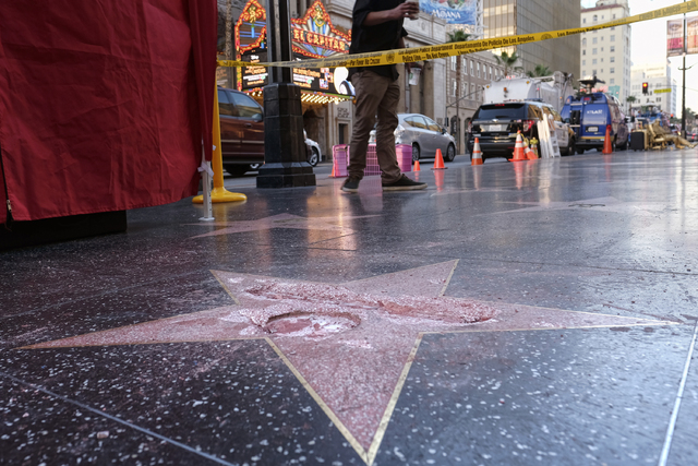 A man stands near a cordoned off area surrounding the vandalized star for Republican presidential candidate Donald Trump on the Hollywood Walk of Fame, Wednesday, Oct. 26, 2016, in Los Angeles. (R ...