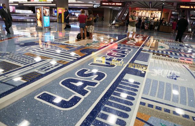 Passengers walk past the floor design depicting number of Las Vegas landmarks at McCarran International Airport on Friday, Sept. 9, 2016. (Bizuayehu Tesfaye/Las Vegas Review-Journal Follow @bizute ...
