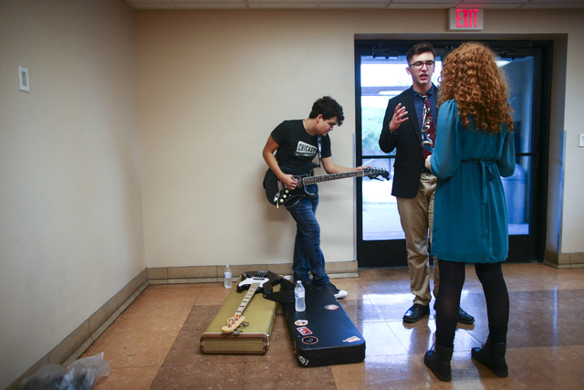 Before a Notes With a Purpose performance at the Las Vegas Rescue Mission, Las Vegas Academy graduate Anthony Aceves, left, practices on his guitar while friends Michael Westlake and Paige Thomson ...