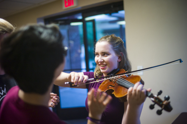 Before playing the piano for Las Vegas Rescue Mission diners, Las Vegas Academy student Megan Pridmore practices on the violin with a fellow Notes With a Purpose musician. Chase Stevens/Las Vegas  ...