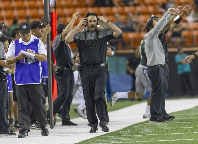 Hawaii head coach Nick Rolovich adjust his headphones during in the third quarter of an NCAA college football game against Nevada, Saturday, Oct. 1, 2016, in Honolulu. (Eugene Tanner/AP)