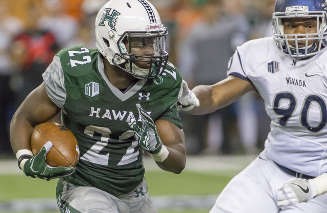 Hawaii running back Diocemy Saint Juste (22) attempts to get past Nevada defensive end Malik Reed (90) in the second quarter of an NCAA college football game, Saturday, Oct. 1, 2016, in Honolulu.  ...