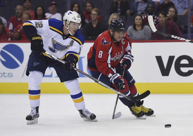 In this Oct. 3, 201`6, file photo, Washington Capitals left wing Alex Ovechkin (8), of Russia, eyes the puck next to St. Louis Blues center Jori Lehtera (12), of Finland, during the first period o ...
