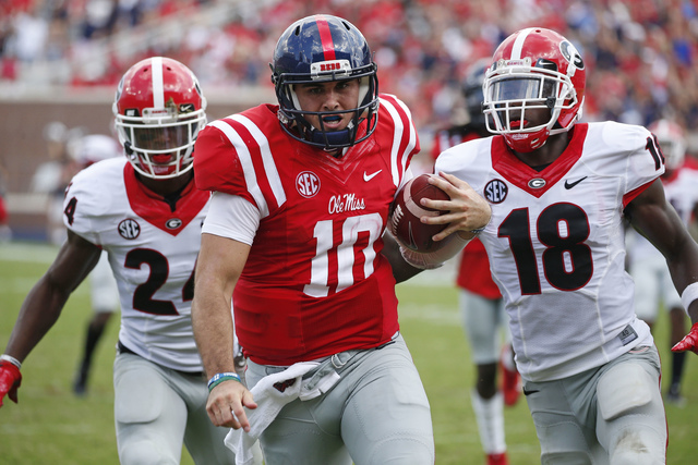 In this Sept. 24, 2016, file photo, Mississippi quarterback Chad Kelly (10) runs past Georgia cornerback Deandre Baker (18) and safety Dominick Sanders (24) for a 41-yard touchdown run during the  ...