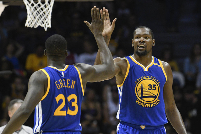 Golden State Warriors forward Kevin Durant (35) high-fives Draymond Green (23) after scoring during the second half of an NBA preseason basketball game against the Los Angeles Lakers on Wednesday, ...
