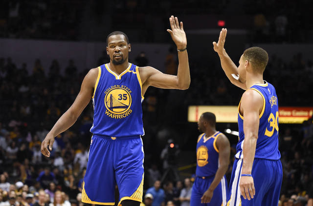 Golden State Warriors forward Kevin Durant, left, high-fives Stephen Curry (30) during the second half of an NBA preseason basketball game against the Los Angeles Lakers on Wednesday, Oct. 19, 201 ...