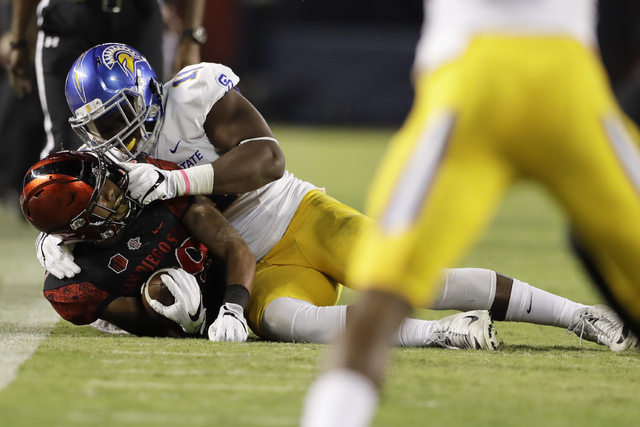 San Jose State linebacker William Ossai, above, puts a hand on the face mask of San Diego State running back Donnel Pumphrey as he hauls him down during the second half of an NCAA college football ...