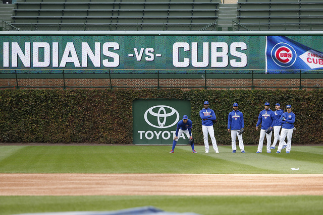 Chicago Cubs players work out in the outfield during batting practice for Friday's Game 3 of the Major League Baseball World Series against the Cleveland Indians, Thursday, Oct. 27, 2016, in Chica ...