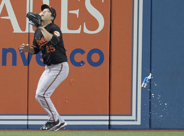 Baltimore Orioles' Hyun Soo Kim gets under a fly ball as a can falls past him during the seventh inning of an American League wild-card baseball game against the Toronto Blue Jays in Toronto, Tues ...