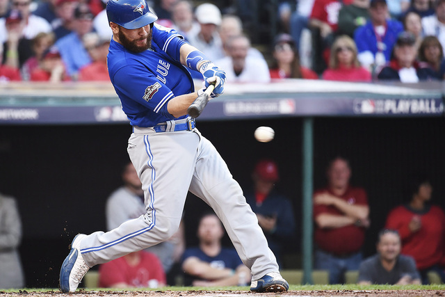 Toronto Blue Jays catcher Russell Martin (55) hits a single against the Cleveland Indians during the second inning of Game 2 of baseball's American League Championship Series in Cleveland, Saturda ...