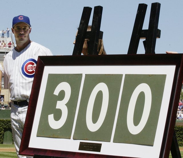 Chicago Cubs pitcher Greg Maddux looks at the framed 300 that was made up from Wrigley Field scoreboard numbers during a presentation prior to the game with the Los Angeles Dodgers, Sunday, Aug. 1 ...