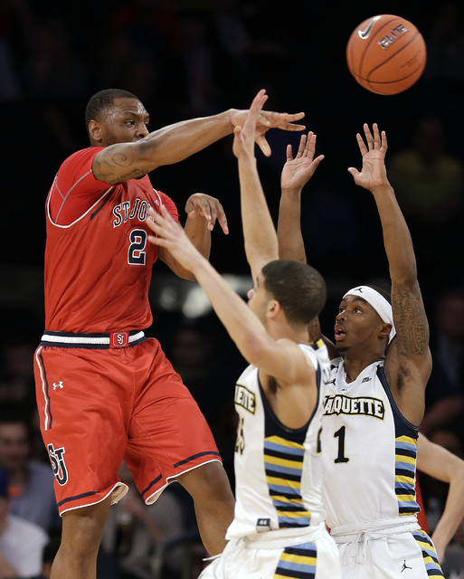 St. John's forward Christian Jones (2) passes the ball over Marquette guard Haanif Cheatham (25) and guard Duane Wilson (1) in the first half of an NCAA college basketball game during the Big East ...