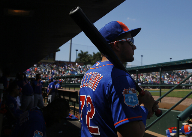 New York Mets' Gavin Cecchini watches from the dugout during the third inning of an exhibition spring training baseball game against the Miami Marlins, Tuesday, March 15, 2016, in Jupiter, Fla. (B ...