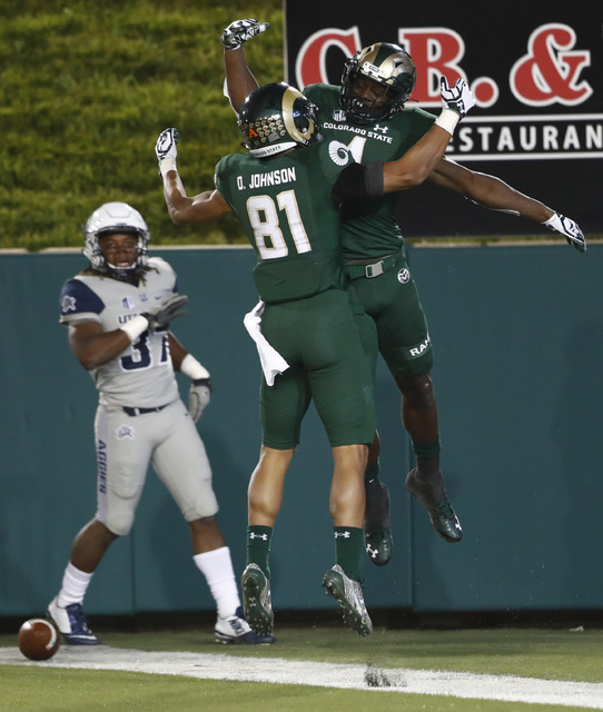 Colorado State wide receiver Michael Gallup, back right, celebrates his touchdown pass reception with wide receiver Olabisi Johnson as Utah State safety Devin Centers looks on in the second half o ...