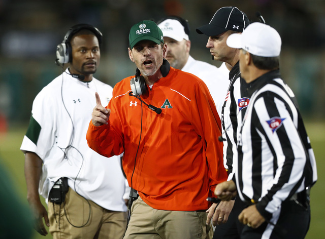 Colorado State head coach Mike Bobo, center, argues for a call with referees while facing Utah State in the second half of an NCAA college football game Saturday, Oct. 8, 2016, in Fort Collins, Co ...