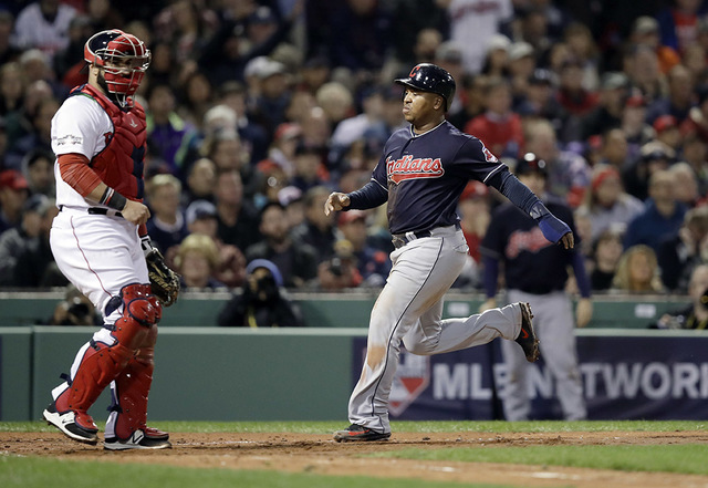 Cleveland Indians' Jose Ramirez, right, runs home to score in front of Boston Red Sox catcher Sandy Leon during the fourth inning in Game 3 of baseball's American League Division Series, Monday, O ...