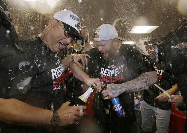 Cleveland Indians manager Terry Francona, left, and Mike Napoli get doused during a clubhouse celebration after the Indians beat the Boston Red Sox 4-3 in Game 3 of baseball's American League Divi ...