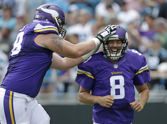 ADVANCE FOR WEEKEND EDITIONS, OCT. 15-16 - FILE - In this Sept. 25, 2016, file photo, Minnesota Vikings' Sam Bradford (8) is congratulated by Jeremiah Sirles (78) after touchdown pass against the  ...