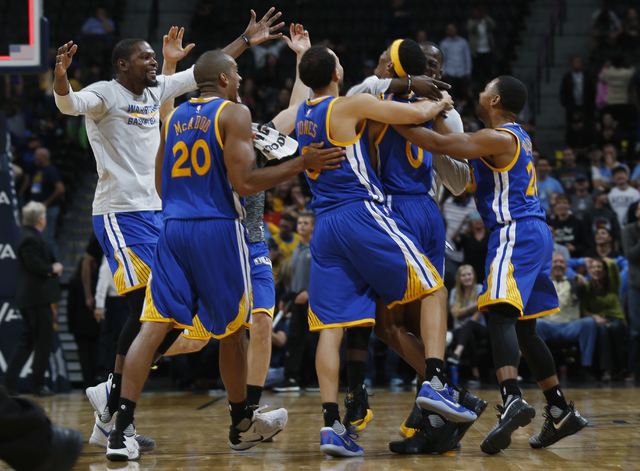 Golden State Warriors surround guard Patrick McCaw, fourth from left, after he hit the winning basket against the Denver Nuggets as time ran out in overtime of an NBA preseason basketball game Fri ...