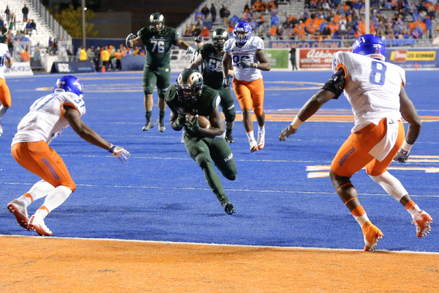 Colorado State running back Dalyn Dawkins runs for a touchdown as Boise State safety Cameron Hartsfield, left, and defensive end Jabril Frazier defend during the second half of an NCAA college foo ...