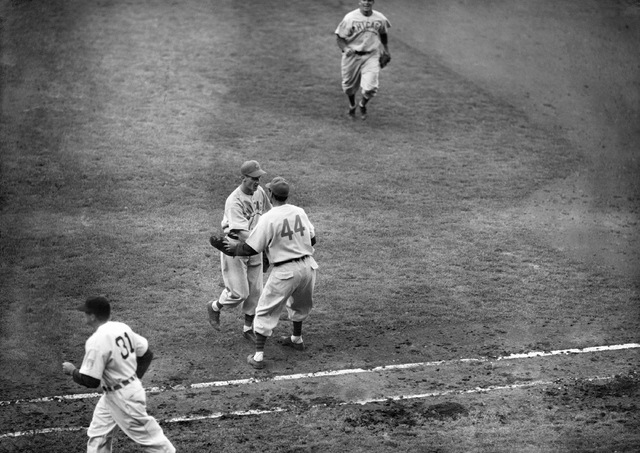In this Oct., 3, 1945, file photo, Phil Cavarretta (44), of the Chicago Cubs, rushes over from first base to pitcher Hank Borowy to congratulate him on his six-hit, 9-0, victory over the Detroit T ...