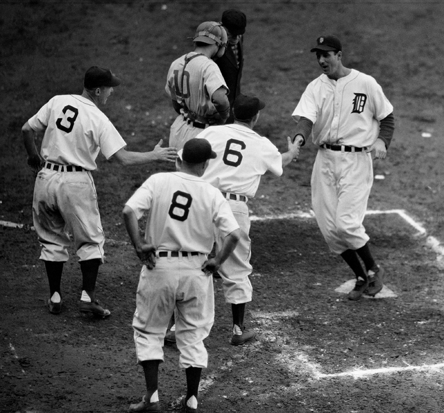 Detroit Tigers left fielder Hank Greenberg, right, finds three teammates, Eddie Mayo (3), Roger Cramer (8), and Ray Cullenbine (6), on hand to welcome him as he crosses the plate with a fifth-inni ...