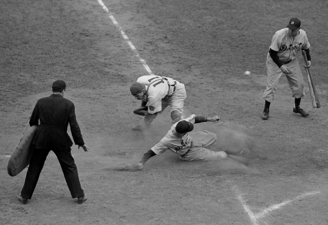 Detroit Tiger second baseman Eddie Mayo slides safely across home plate in the eighth inning of the final World Series game here on Oct. 10, 1945 at Chicago. As Chicago Cubs catcher Mickey Livings ...