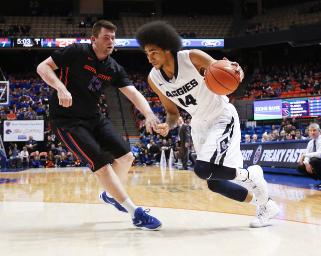 Utah State's Jalen Moore (14) drives the ball against Boise State's Nick Duncan during the first half of an NCAA college basketball game in Boise, Idaho, on Tuesday, Feb. 2, 2016. (AP Photo/Otto K ...