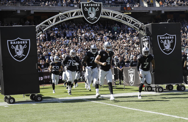 Oakland Raiders quarterback Derek Carr (4) and teammates run onto the field before an NFL football game against the San Diego Chargers in Oakland, Calif., Sunday, Oct. 9, 2016. (AP Photo/Marcio Jo ...