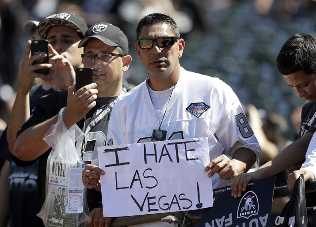 An Oakland Raiders fan holds up a sign about the team possibly relocating to Las Vegas before an NFL football game between the Oakland Raiders and the Atlanta Falcons in Oakland, Calif., Sunday, S ...