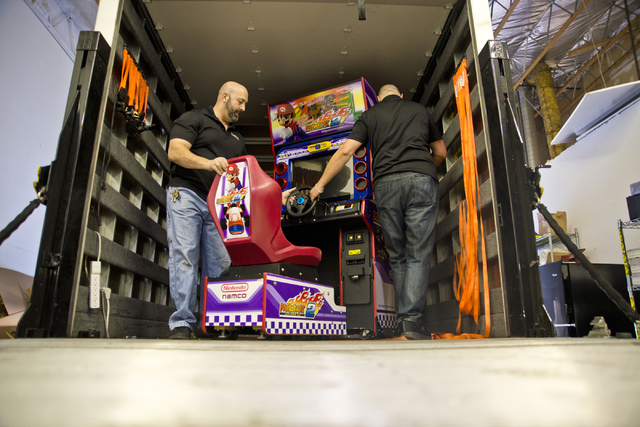 Larry Galbraith, left, and James Angelone, of Superior Games & Vending, unload a racing arcade game inside their repair shop and warehouse in North Las Vegas on Tuesday, Oct. 11, 2016. Daniel  ...