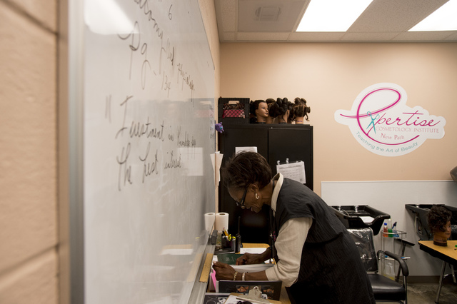 Cosmetology instructor Dorothy Muhammad pages though one of the textbooks during a cosmetology class Thursday, June 30, 2016, at Florence McClure Women's Correctional Center in North Las Vegas. (B ...
