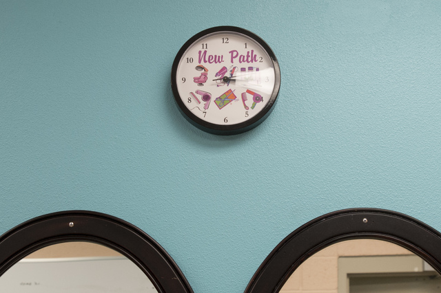 """A clock with the words """"New Path,"""" and illustrations of hair tools sits above the mirror were the inmates practice their skills on Thursday, June 30, 2016, at Florence McClure Women's Correctional ..."""
