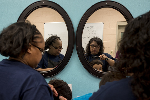Inmates Kimala Kimble, left, and Candice Austin, right,  practice updos on hair mannequins on Thursday, June 30, 2016, at Florence McClure Women's Correctional Center in North Las Vegas. (Bridget  ...