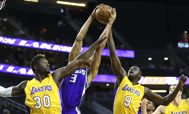 Los Angeles Lakers forwards Julius Randle (30) and Luol Deng (9) fight for a rebound against Sacramento Kings forward Skal Labissiere (3) during a preseason basketball game at the T-Mobile Arena i ...