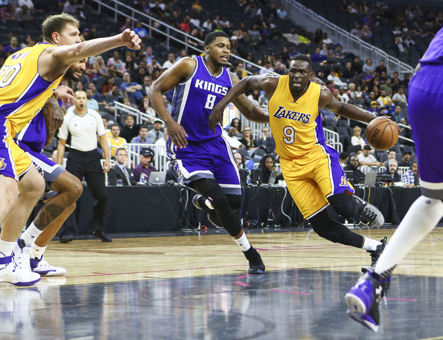 Los Angeles Lakers forward Luol Deng (9) drives past Sacramento Kings forward Rudy Gay (8) during a preseason basketball game at the T-Mobile Arena in Las Vegas on Thursday, Oct. 13, 2016. The Sac ...
