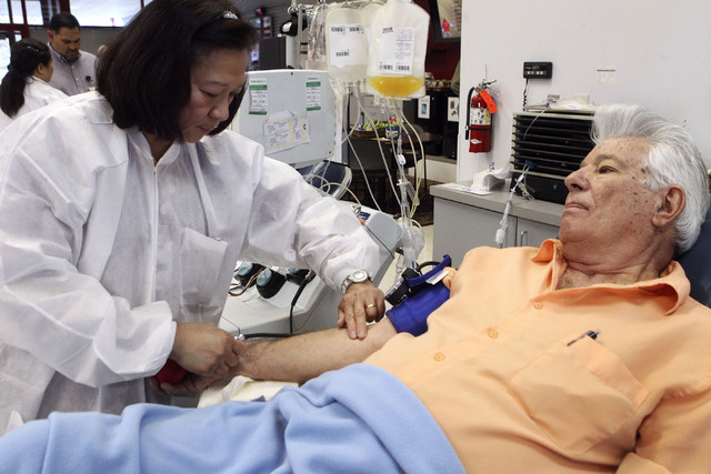 Victoria Jarina, a phlebotomist, checks for veins in donor Gene Mitchell's arm at United Blood Services in Las Vegas, Monday, Nov. 11, 2013. (Jerry Henkel/Las Vegas Review-Journal)