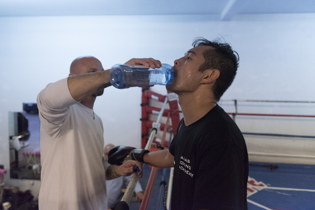 "Nonito Donaire, right, is given water by Clarence ""Bones"" Adams during a training session at Bones Adams Boxing Gym in Las Vegas on Monday, Oct. 17, 2016, to defend Donaire's Super Bantamweight ti ..."