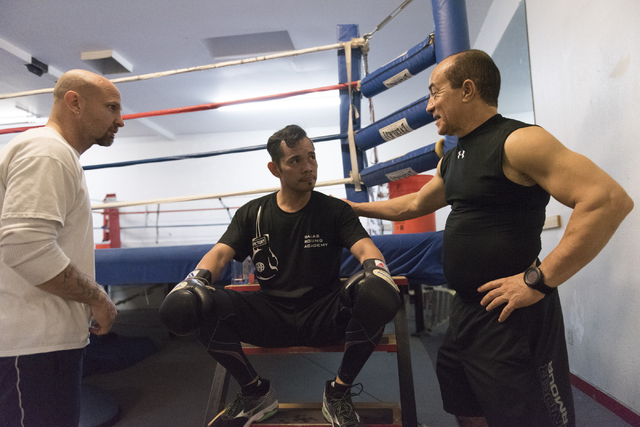 "Nonito Donaire, center, speaks with Ismael Salas, right, and Clarence ""Bones"" Adams during a training session at Bones Adams Boxing Gym in Las Vegas on Monday, Oct. 17, 2016, to defend Donaire's S ..."