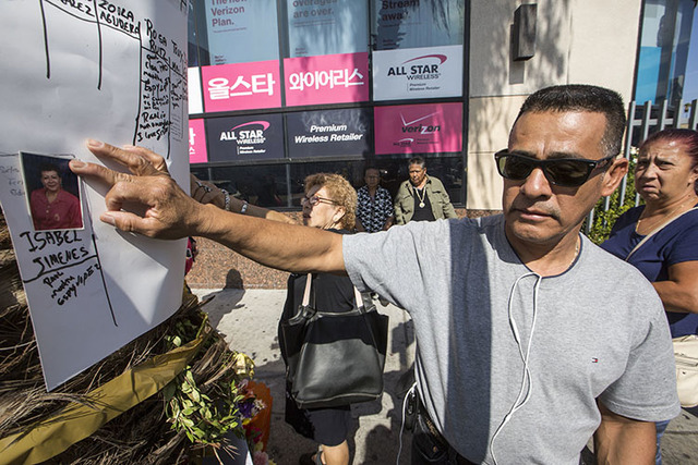 Tomas Hernandez holds a photo of his late sister, Isabel Jimenez Hernandez, who was killed in a gambling tour bus accident, at a makeshift memorial in Los Angeles.  (Damian Dovarganes/The Associat ...