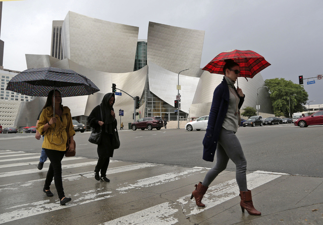 Umbrellas protect people from rain as they walk past the Frank Gehry-designed Disney Hall in downtown Los Angeles on Friday, Oct. 28, 2016. (Nick Ut/The Associated Press)