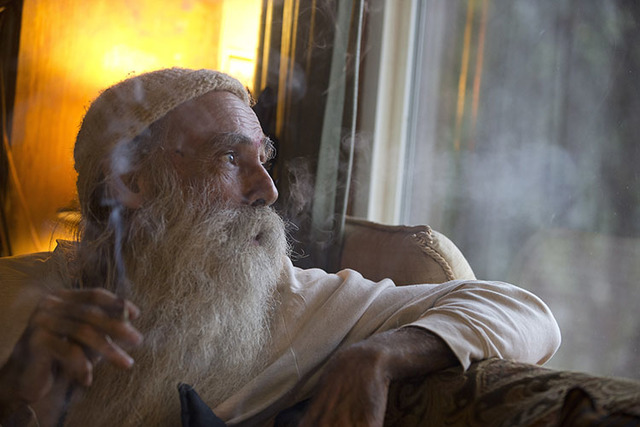 "Swami Chaitanya looks out the window while smoking a ""grower's joint"" marijuana cigarette at his home near Laytonville, Calif. (Rich Pedroncelli/The Associated Press)"