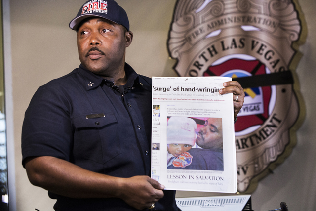 Capt. Cedric Williams, public information officer for the North Las Vegas Fire Department, holds a copy of a Review-Journal story profiling his friend and colleague Capt. Yaphet Miller on Thursday ...