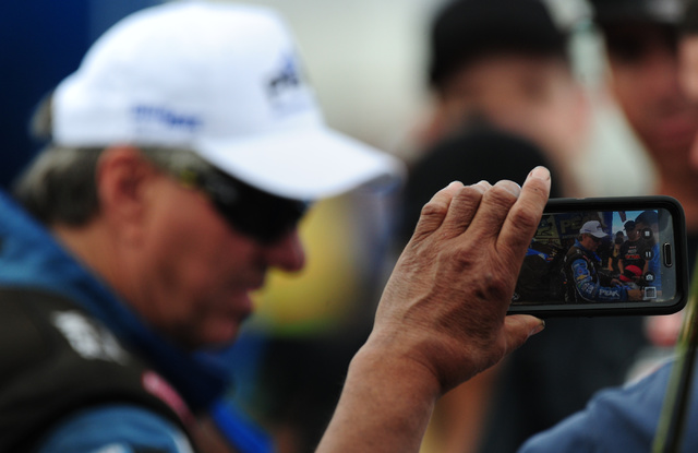 A fan takes a cell phone photo of Funny Car driver John Force signing autographs in between qualifying session for the NHRA Mello Yello Series Toyota Nationals at The Strip at Las Vegas Motor Spee ...