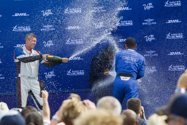 Pilots Daniel Ryfa, left, and Kevin Coleman, right, spray champagne on Florian Berger after receiving their race results for the Challenger Cup air race during a podium celebration at the Las Vega ...