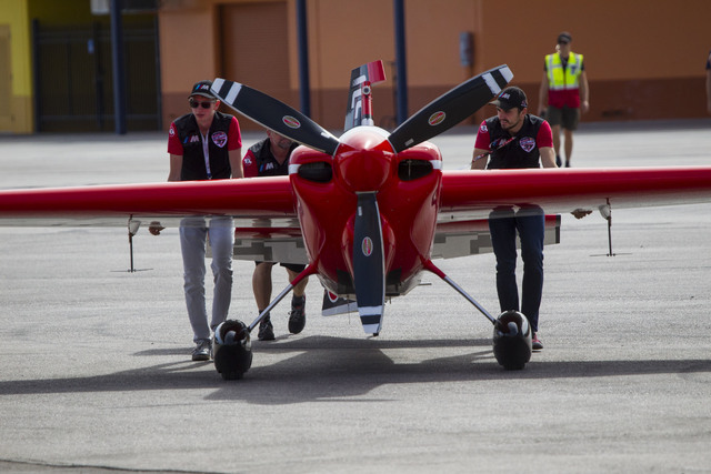 Crew for Peter Podlunsek Racing push their Zivko Edge 540 V2 aircraft back to it's hanger during a wind delay on the final day of the Red Bull Air Race World Championship at the Las Vegas Motor Sp ...