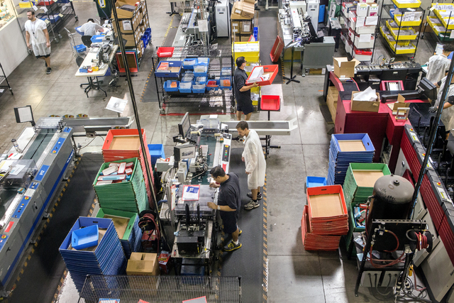 People work in the secure credit card processing area at   Arroweye Solutions in Henderson on Friday, Oct. 21, 2016. The company is the world's largest on-demand credit and debit producer. (Jeff S ...